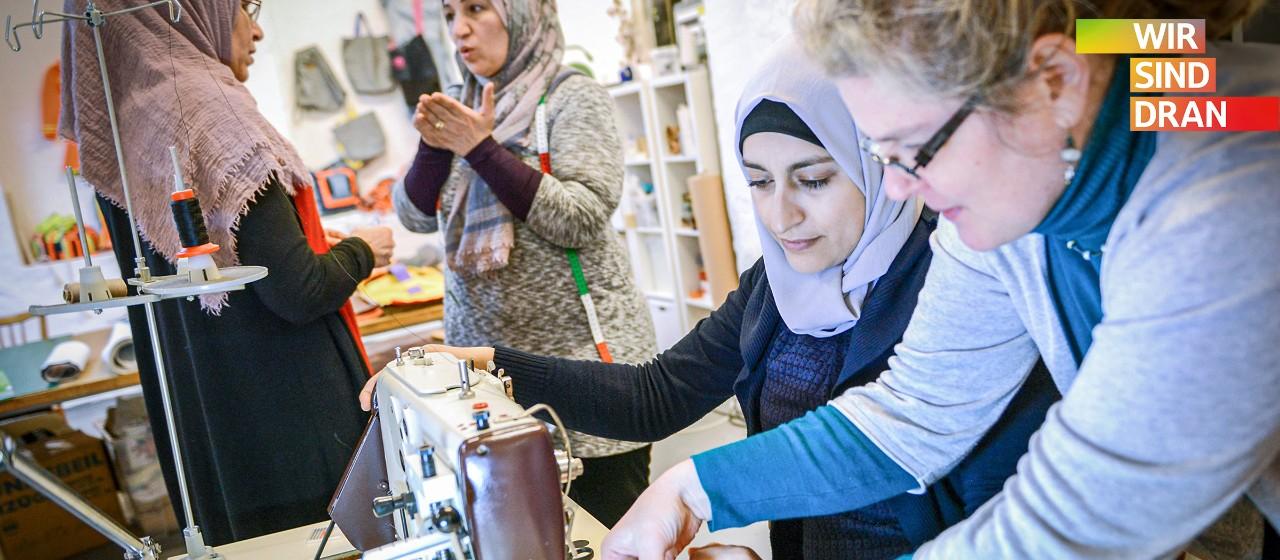 Eine Gruppe Frauen in einer Nähwerkstatt. Zwei Frauen mit Kopftuch sind im Gespräch. Eine Frau mit locken und Brille und eine weitere Frau mit Kopftuch erbeiten an einer Nähmaschine. | Sparkasse Hannover