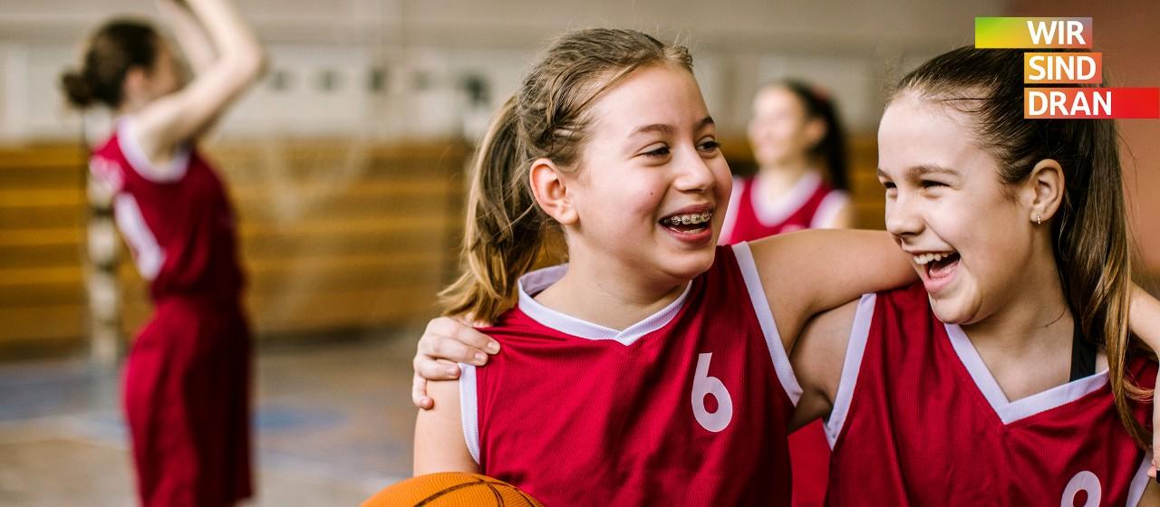 Zwei Basketball- Trickots tragende Mädchen lachen Arm in Arm und mit einem Basketball in der Hand in einer Turnhalle.| Sparkasse Hannover
