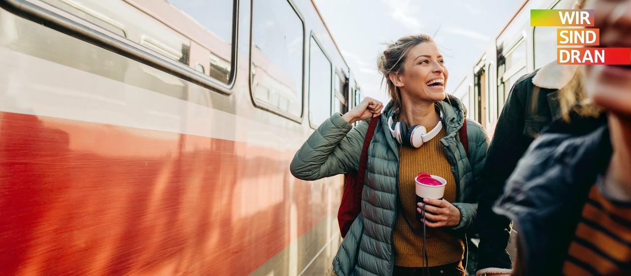 Junge Frau mit Rucksack auf dem Rücke und einem Thermosbecher in der Hand steht zwischen zwei Zügen auf einem Gleis und lacht jemanden fröhlich an | Sparkasse Hannover