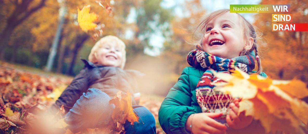 Kleinkinder spielen im Laub  | Sparkasse Hannover