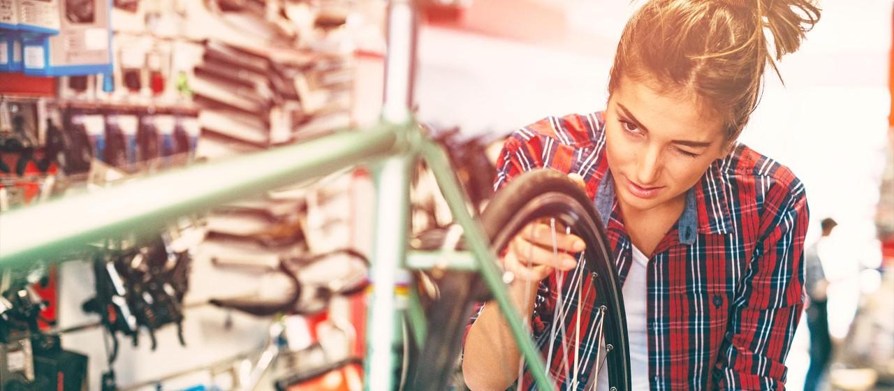 Junge Leute: Azubis - Auszubildende Mechanikerin repariert ein Fahrrad | Sparkasse Hannover