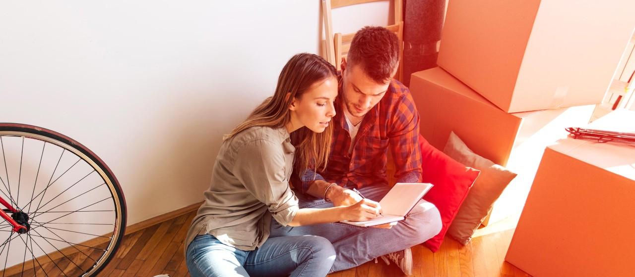 Junge Leute: Azubis - Junges Paar sitzt auf dem Boden neben Umzugskartons und schreibt in ein Buch | Sparkasse Hannover