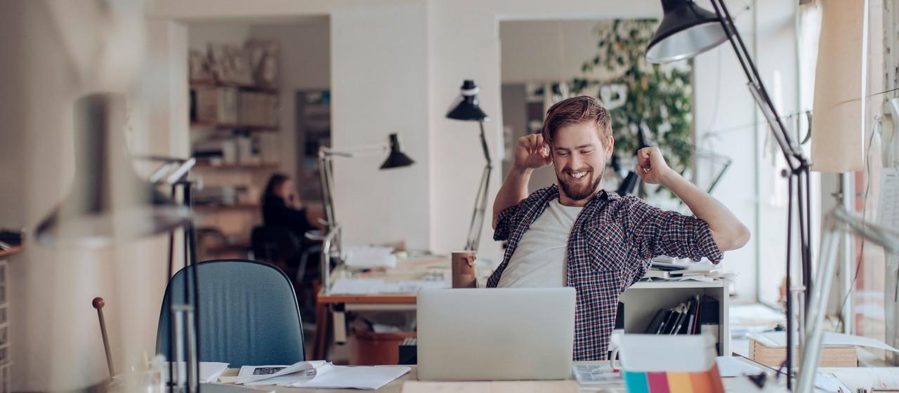 Nahaufnahme eines lächelnden jungen Mannes der an einem Schreibtisch sitzt | Sparkasse Hannover