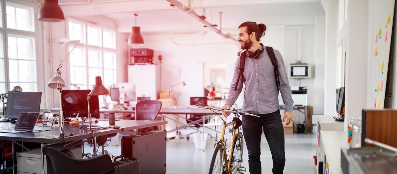 Junge Leute: Berufseinsteiger - Junger Mann mit einem Fahrrad in einem Büro | Sparkasse Hannover