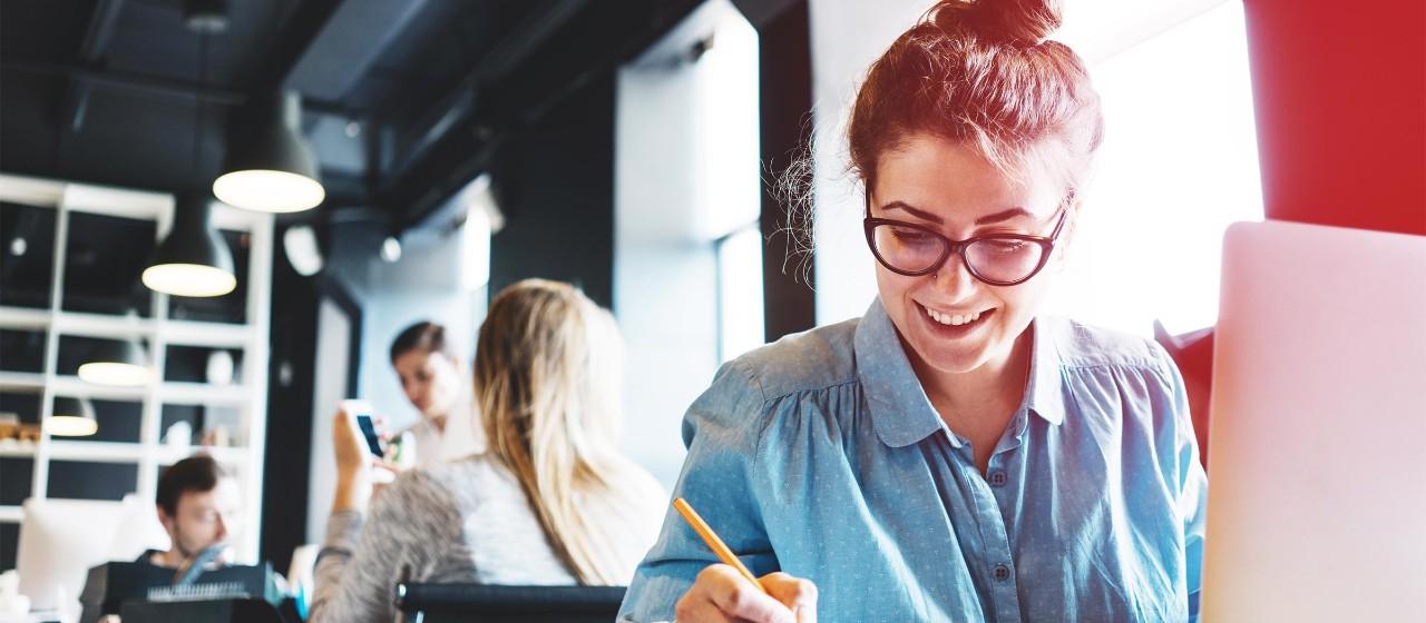 Junge Leute: Berufseinsteiger -  Nahaufnahme einer jungen Frau mit Brille, die an einem Laptop sitzt und Notizen aufschreibt | Sparkasse Hannover