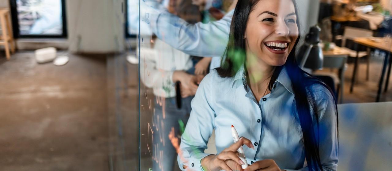 Lachende junge Frau hinter einer Glaswand in einem Büro  | Sparkasse Hannover