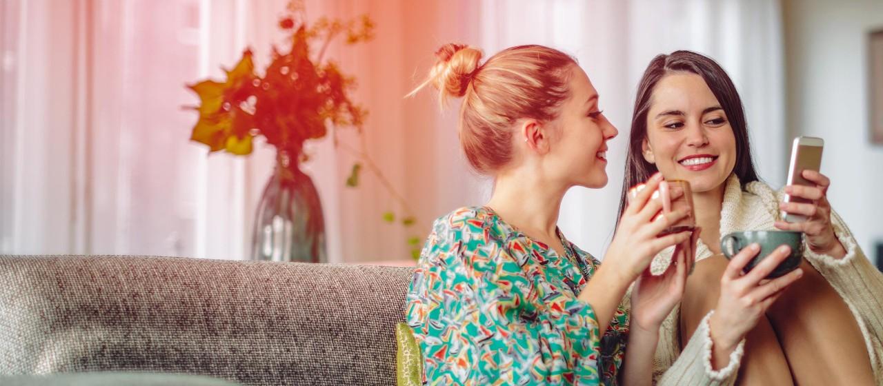 Junge Leute: Berufseinsteiger - Zwei junge Frauen sitzen auf einer Couche und schauen gemeinsam in ein Smartphone | Sparkasse Hannover