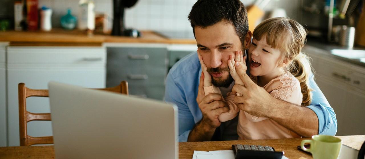 Junger Mann sitzt mit Kleinkind auf dem Schoß vor einem Laptop | Sparkasse Hannover
