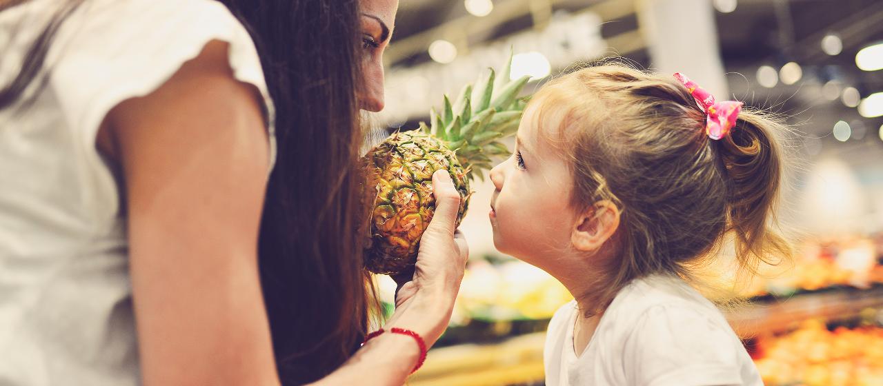 Junge Leute: Kleinkinder - Mädchen schaut Frau mit Ananas in der Hand an | Sparkasse Hannover