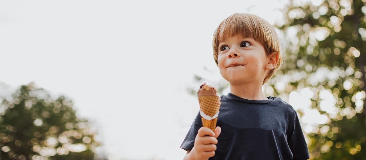 Junge Leute: Schüler - Junge hält ein Eis in der Hand und guckt aus dem Bild | Sparkasse Hannover