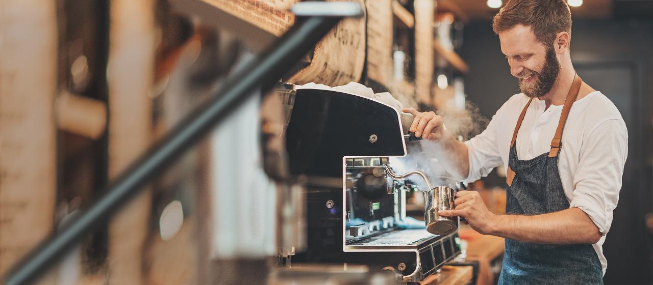 Junge Leute: Studenten - Junger Mann mit Schürze steht vor einem Kaffeeautomaten und bereitet Kaffee zu | Sparkasse Hannover