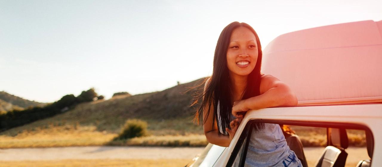 Junge Leute: Studenten - Junge Frau steht in der Tür eines Autos und lacht | Sparkasse Hannover