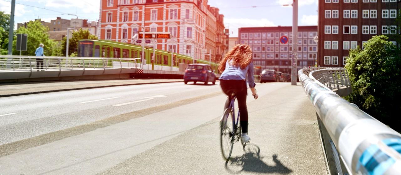 Junge Leute: Frau auf Fahrrad fährt über Benno-Ohnesorg-Brücke  in Hannover| Sparkasse Hannover