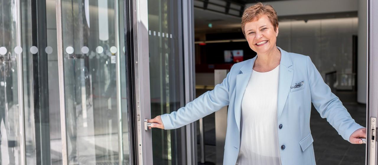 Mitarbeiterin einer Sparkasse Filiale steht lächelnd in der Tür | Sparkasse Hannover