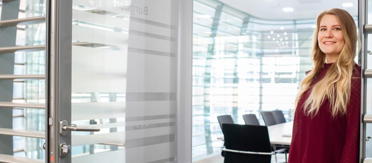 Junge Frau lehnt an Türrahmen in einem Büro   Sparkasse Hannover