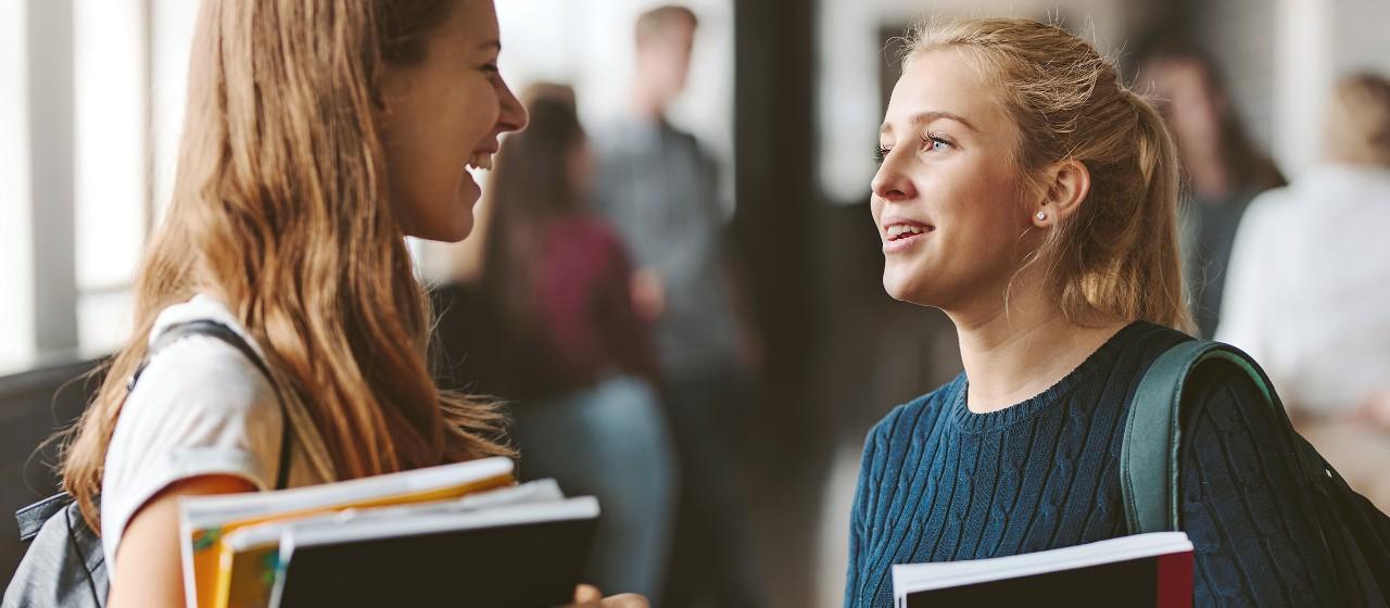 Zwei junge Frauen mit Rucksäcken und Büchern im Arm, blicken sich im freundschaftlichen Gespräch an | Sparkasse Hannover