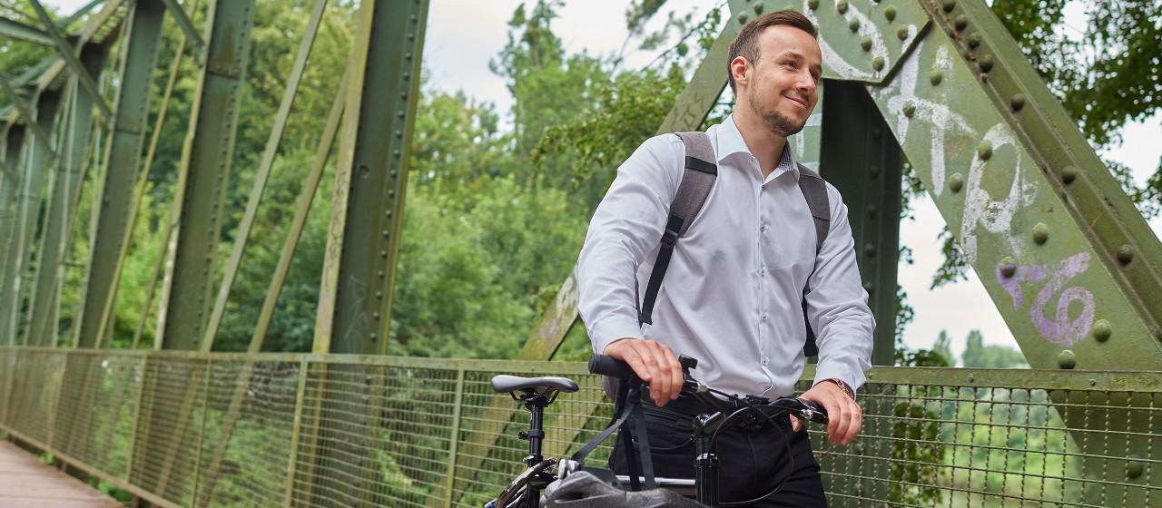 Junger Mann mit Fahrrad auf einer Brücke   Sparkasse Hannover
