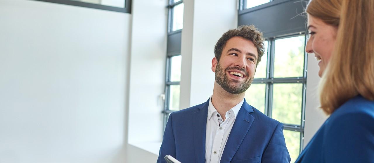 Junger Mann und junge Frau im Büroumfeld, lächeln sich im freundlichen Gespräch an   Sparkasse Hannover