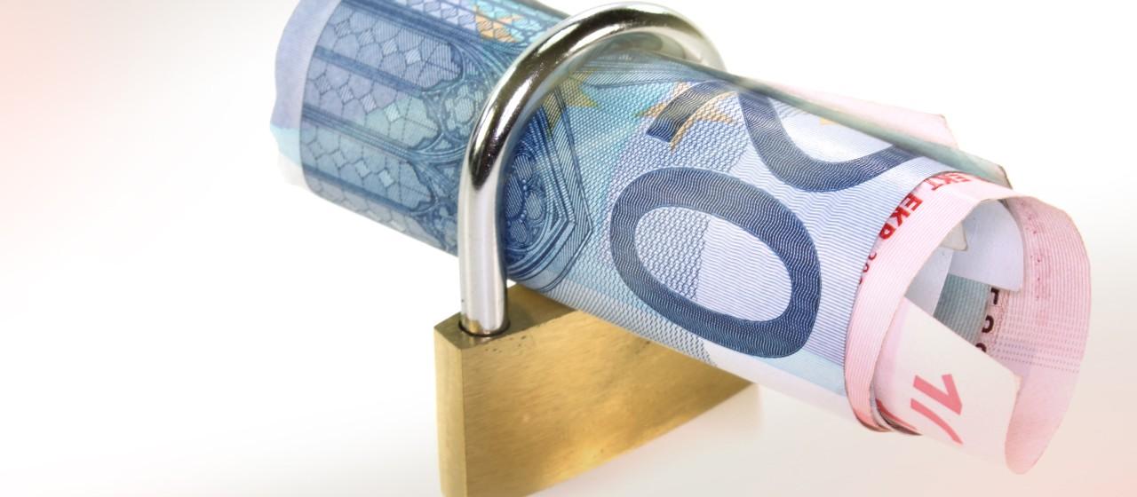 Geldscheine stecken in einem Vorhängeschloss