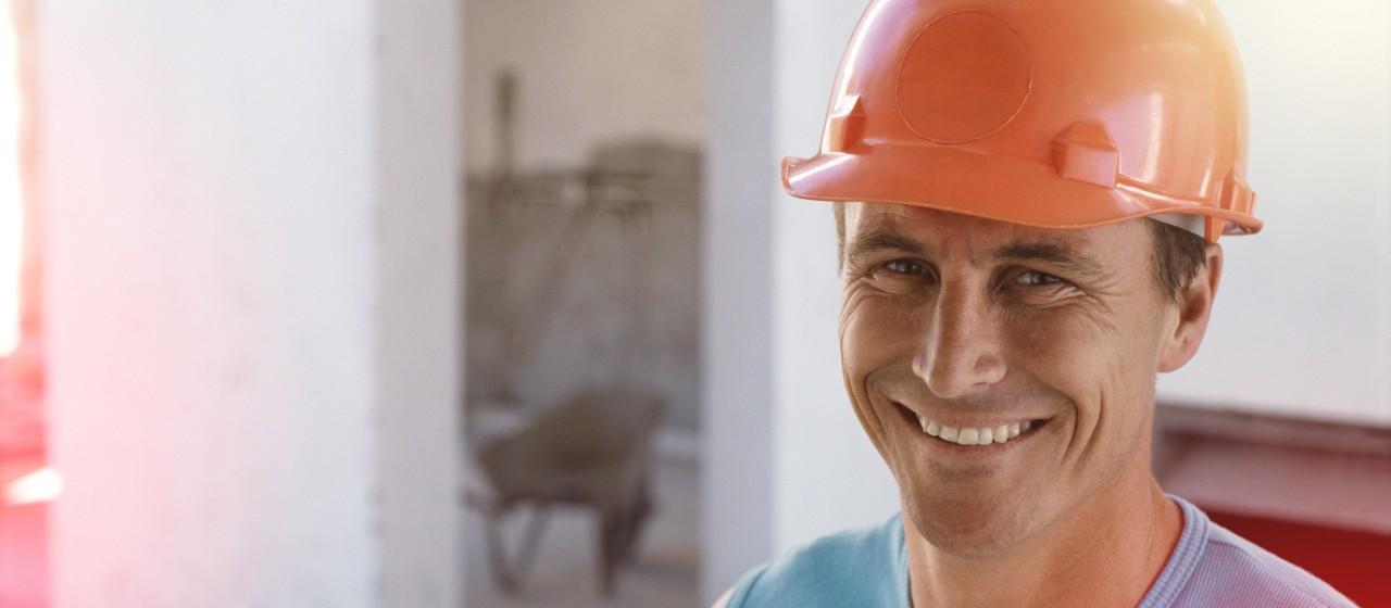 Lächelnder Bauarbeiter mit orangenem Bauhelm
