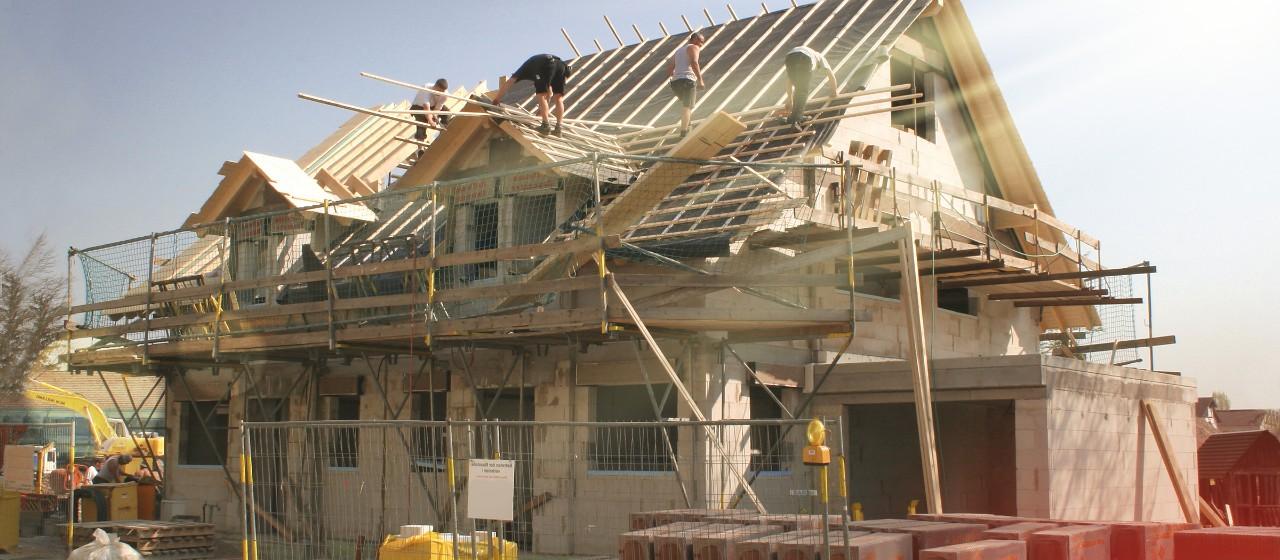 Einfamilienhaus im Rohbau mit Bauarbeitern