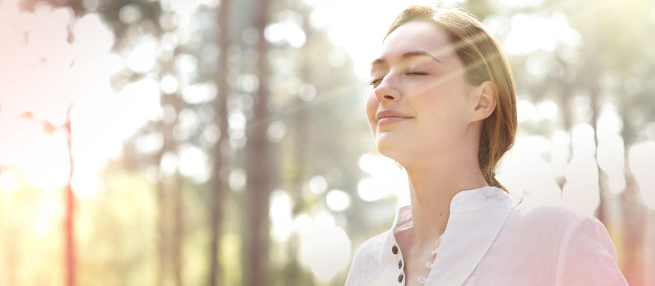 Entspannte Frau steht mit geschlossenen Augen in der Natur