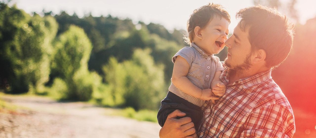 Junger Vater mit einem kleinen jungen auf dem Arm